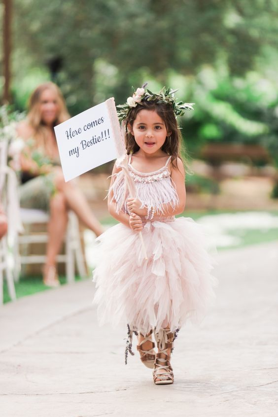 a unique boho flower girl dress with a fringe bodice on spaghetti straps and a blush ruffled skirt