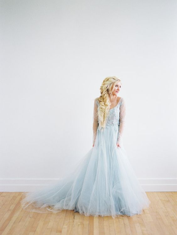 an Elsa-inspired bridal look with a blue wedding dress with a scopp neckline and a tulle skirt plus a dimensional loose Elsa braid