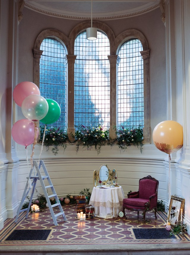 the Beauty and the Beast photo booth with a vintage mirror, chair, clocks and books plus balloons