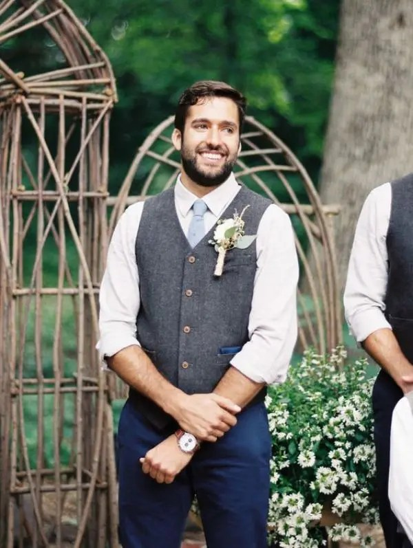 a chic barn groom's look with navy pants, a grey woolen waistcoat, a white button down and a light blue tie