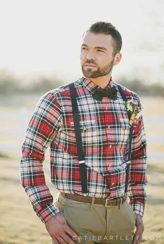 a relaxed barn groom's look with a red plaid button down, tan pants, black suspenders and a bow tie