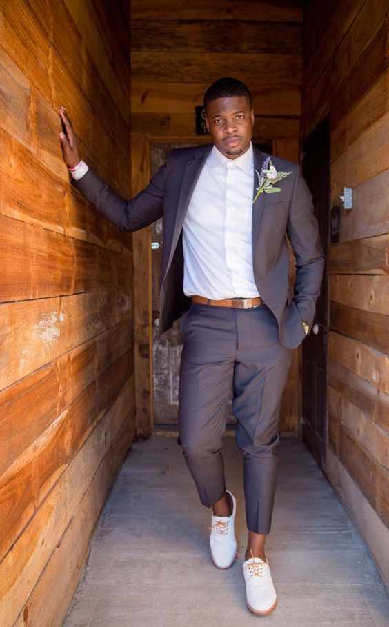 a modern barn groom's look with a chocolate brown suit, a white button down, creamy shoes and amber touches
