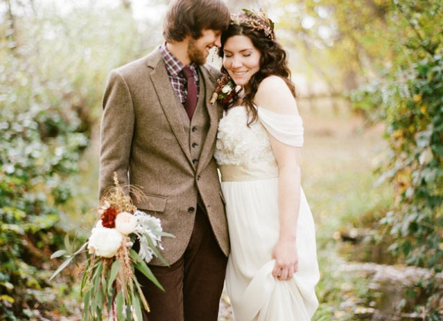 a relaxed groom's outfit with brown pants, a tan tweed blazer and waistcoat, a checked button down, a burgundy tie