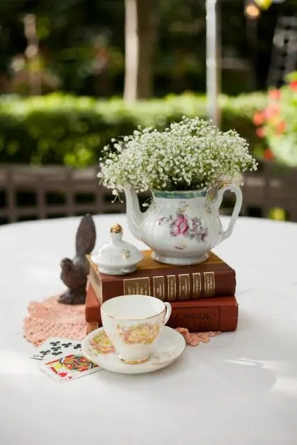 a stylish centerpiece of a couple of vintage books, a teacup, a teapot with baby's breath and a pink doily