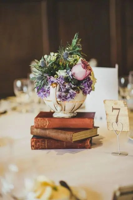 a stylish wedding centerpiece of a stack of books, a teapot with purple and pink flowers and greenery