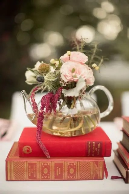 a couple of vintage books with a glass teapot with blooms in burgundy and blush