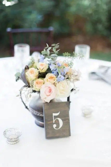 a chic rustic centerpiece of a dark weathered silver teapot with blush and blue blooms and a wooden table number