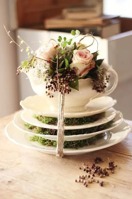 saucepans with moss, a teapot with blush roses and greenery and baker's twine to secure