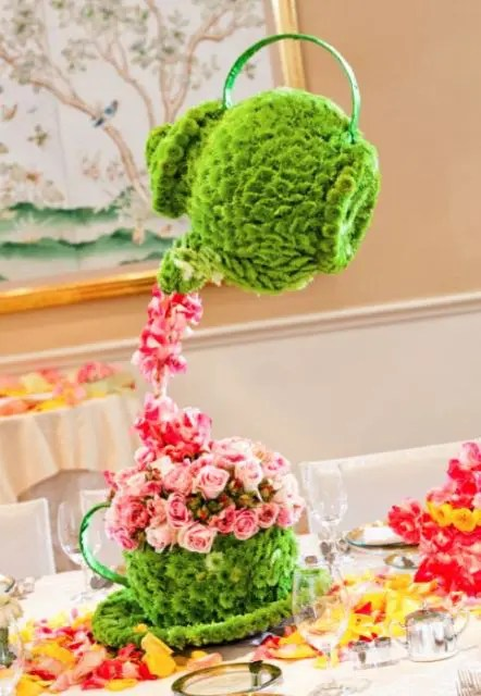 a whimsy wedding centerpiece made of green blooms shaped as tea pots and pink blooms as tea