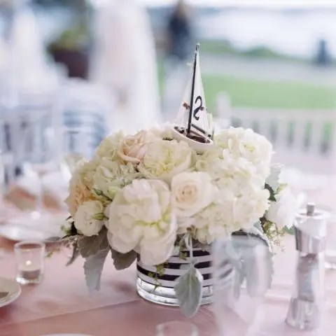 a simple and chic centerpiece of white blooms, a striped vase and a small boat on top