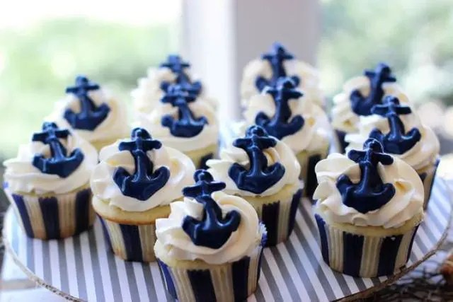 cupcakes with icing and blue edible anchors are nice for a nautical bridal shower or wedding
