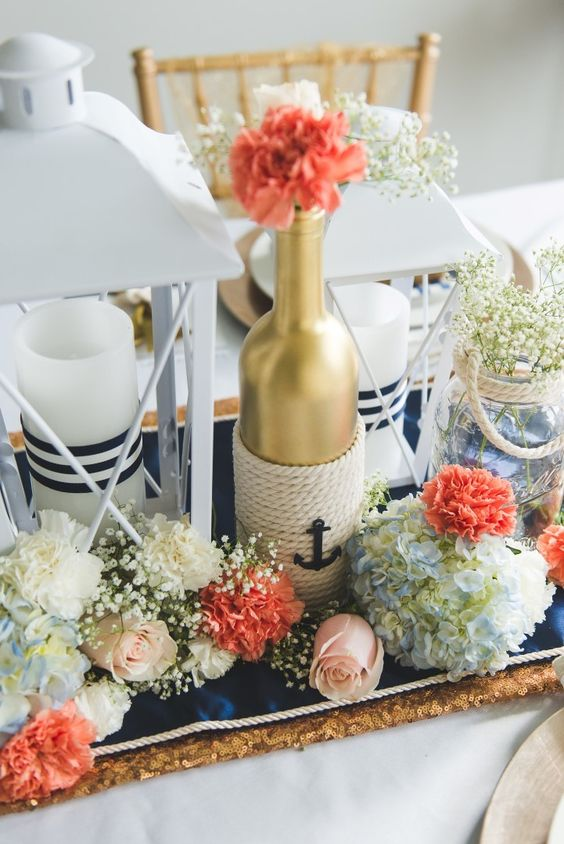 a chic centerpiece with white, coral and blue blooms, a gold bottle with rope, a candle lantern and a jar with baby's breath