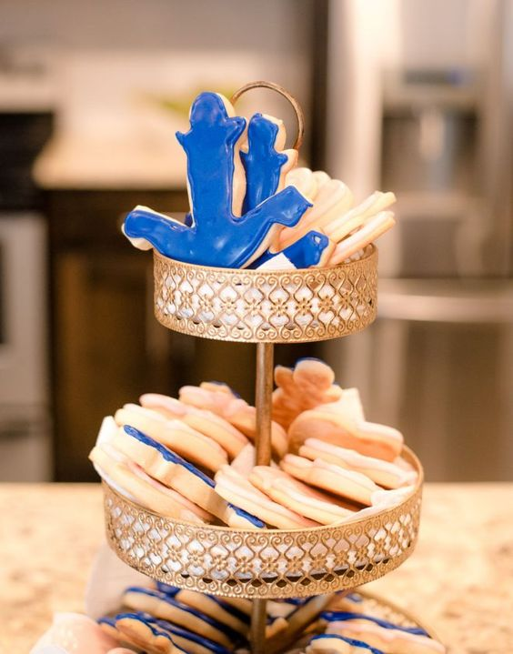 a chic stand with anchor shaped cookies in blue and white is a cool dessert idea for a nautical bridal shower