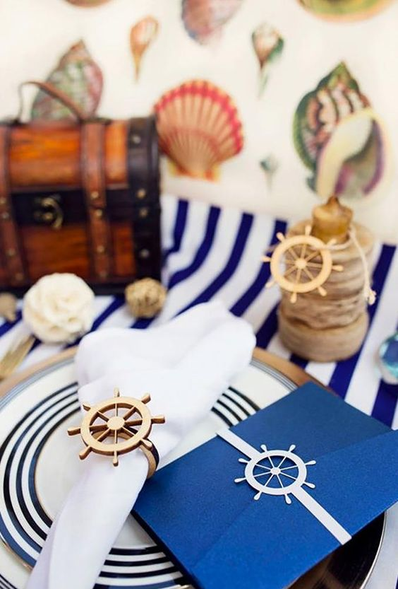 a gilded charger, a striped plate, a wheel napkin ring and a matching stationery piece
