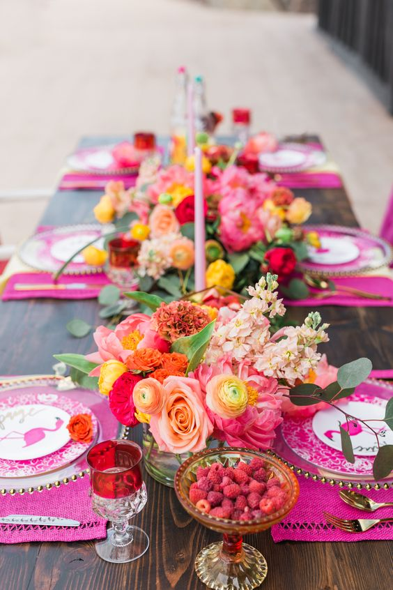 a hot pink bridal shower tablescape with hot pink placemats, bright florals, pink candles, gold cutlery