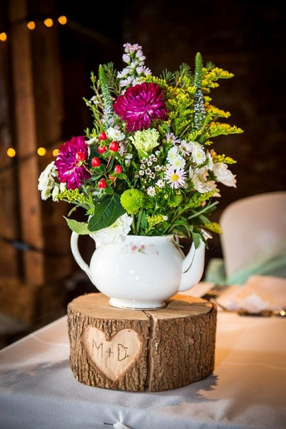 a tree stump with a cutout heart and monograms, a white teapot with greenery and bright flowers