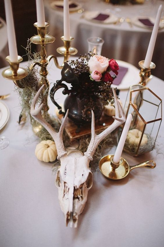 an eclectic wedding centerpiece of a skull, pumpkins, candles, a black teapot with bright blooms