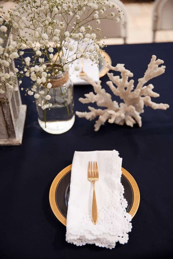 an elegant tablescape done with a navy tablecloth, corals, a gilded charger and cutlery, a baby's breath for a centerpiece