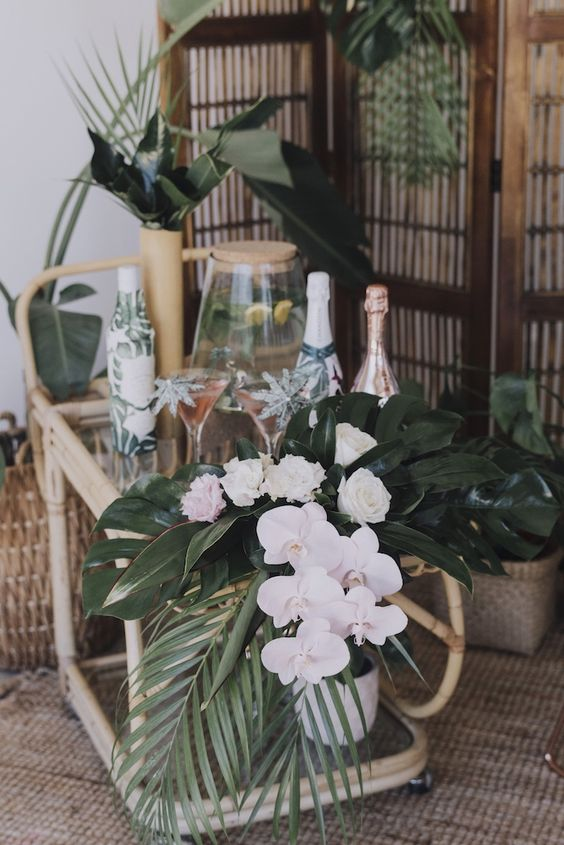 an elegant tropical beverage cart with white blooms, tropical leaves, paper wrapped bottles and leaf arrangements