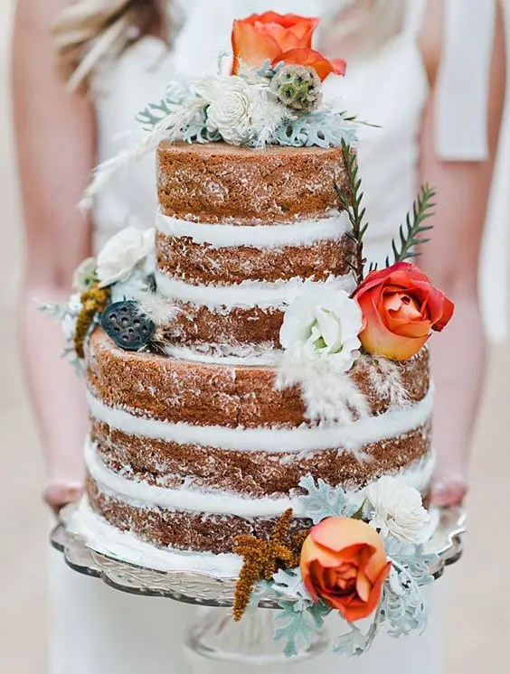 naked wedidng cake with orange roses and pale greenery
