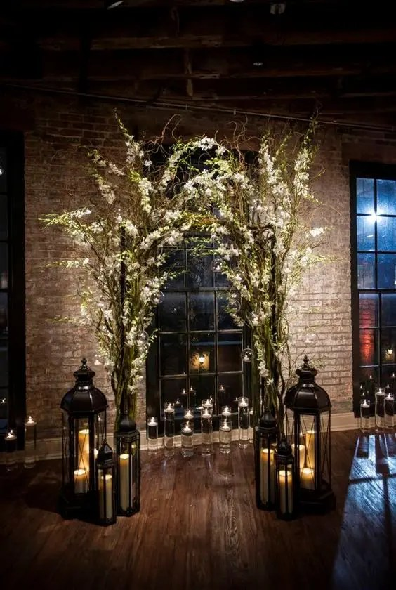indoor branches and flowers arch with lots of candle lanterns