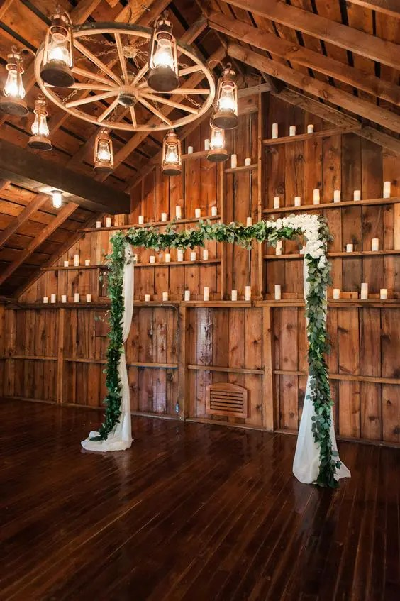 simple eucalyptus garland wedding arch for a barn wedding and candles around for an ambience