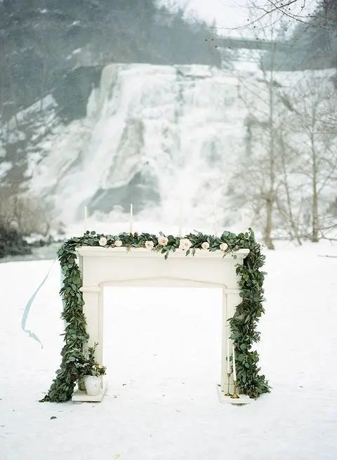 outdoor winter altar decorated with a eucalyptus garland and blush blooms