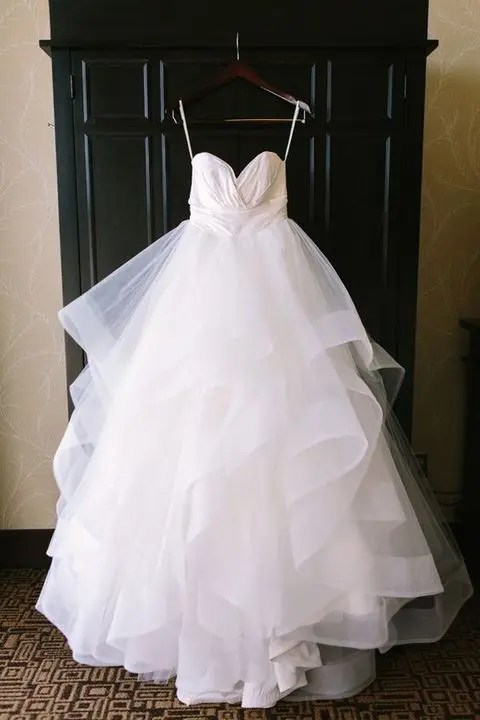 wedding gown hanging in a contrasting backdrop