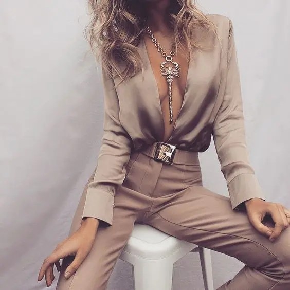 nude jumpsuit with a statement necklace and a belt