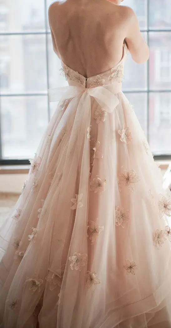 blush floral wedding dress with a bow on the back