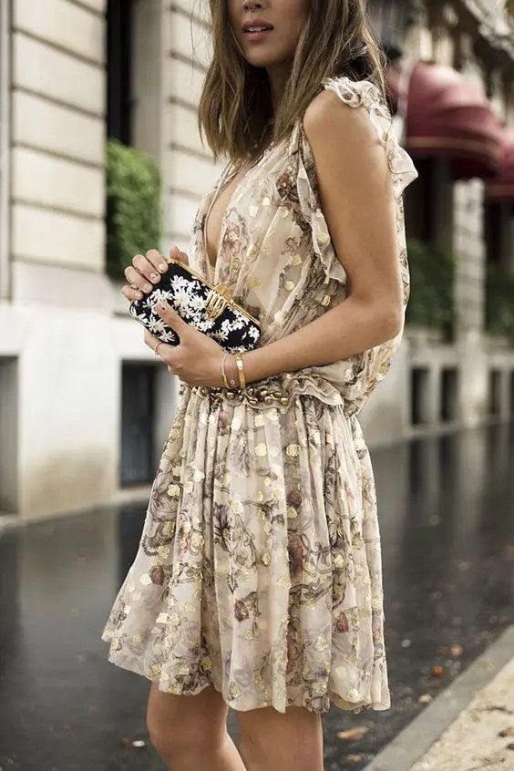 chic neutral dress with a gold leaf print and a plunging neckline