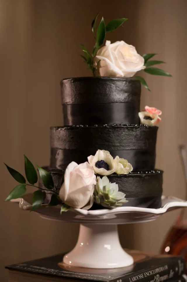 black wedding cake decorated with blush flowers