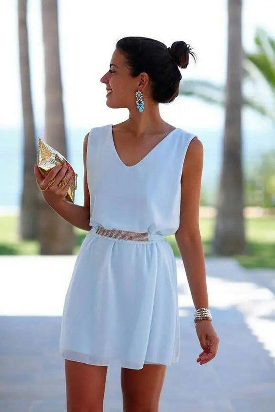 white mini dress with a V-neck and accessories that make the whole outfit