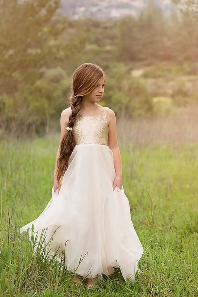 a gold sequin bodice and a flowy ivory skirt