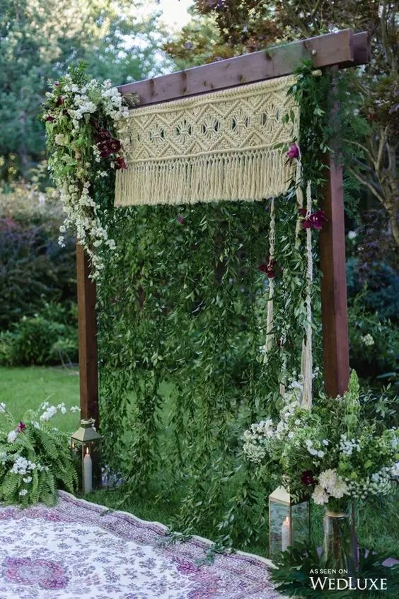 arch with macrame, hanging greenery and bold flowers