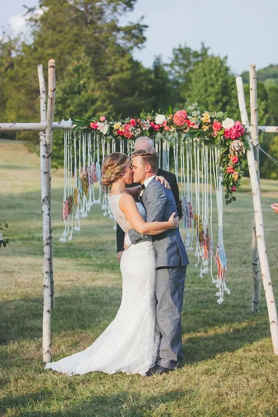 birch branch wedding arch with bold flowers and a macrame hanging