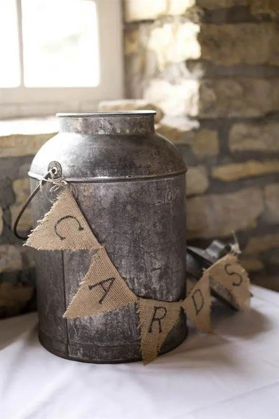 metal milk charn decorated with a burlap banner