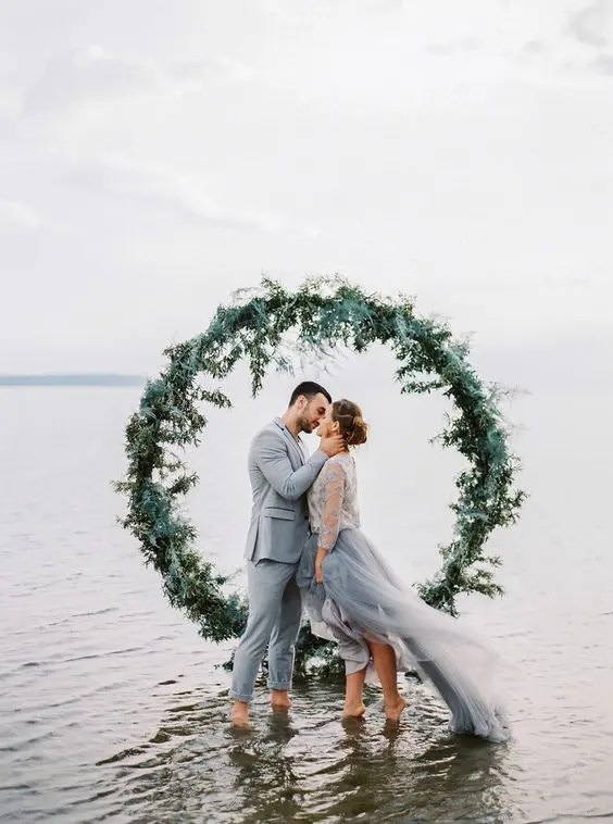 evergreen wreath backdrop right in the sea for a coastal ceremony