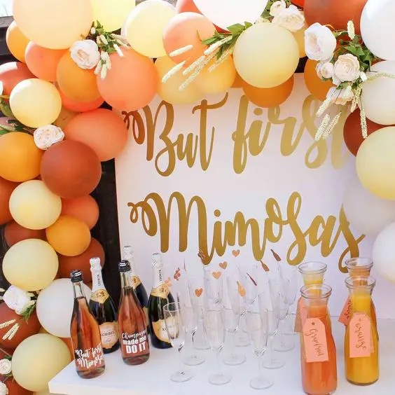a mimosa bar decorated with colorful balloons and blooms