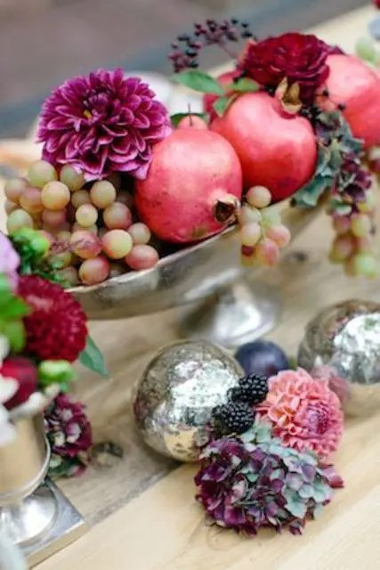 a silver bowl with grapes, pomagranates and burgundy dahlias for a fall wedding
