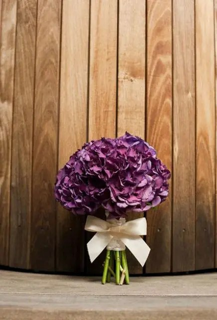 an elegant purple hydrangea wedding bouquet with a white ribbon bow