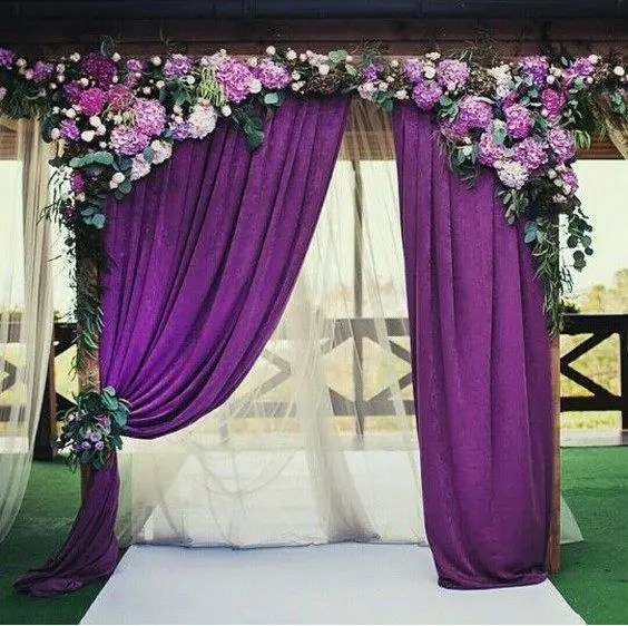 a wedding arch with purple curtains, hydrangeas and greenery