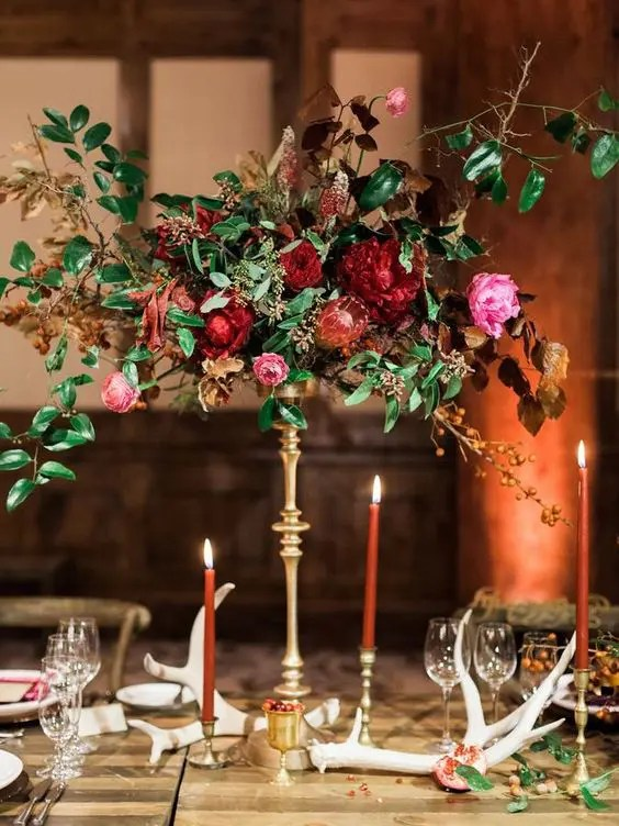 a gorgeous wedding centerpiece with red and pink flowers and textural foliage