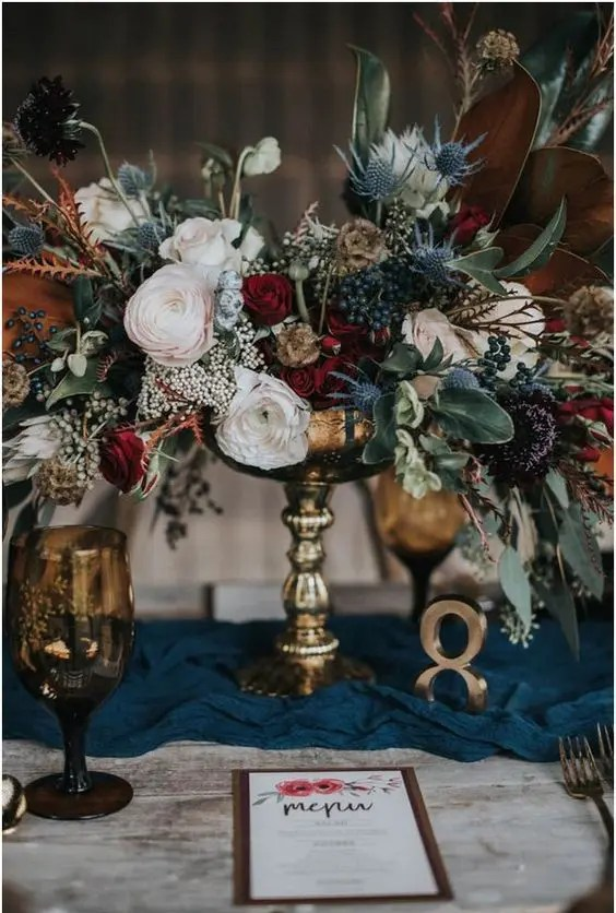a lush textural wedding centerpiece with privet berries, thistles, blush and red blooms and leaves