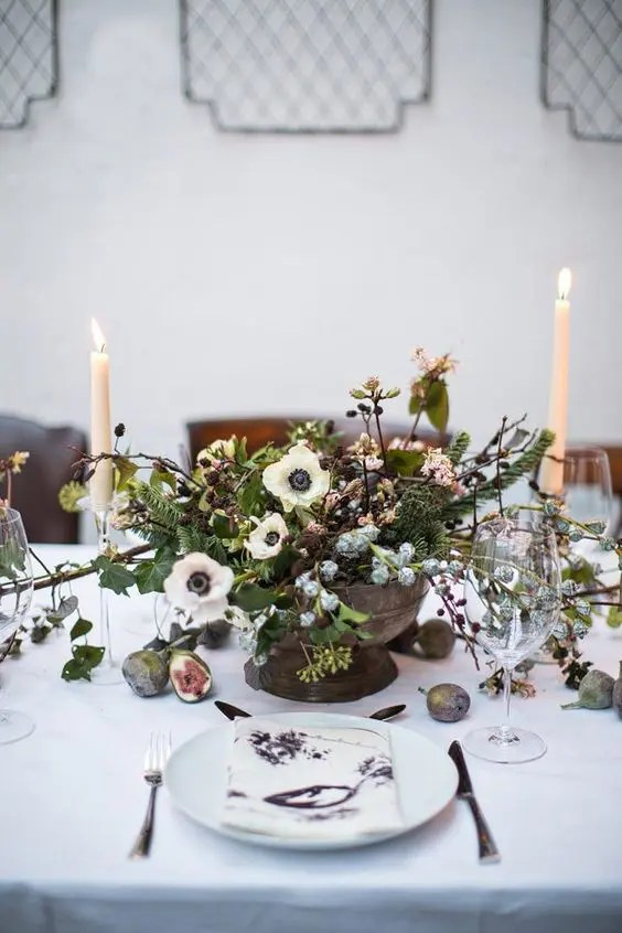 a vintage-inspired centerpiece with white blooms, pinecones, blush flowers, greenery and leaves, all in pale winter shades