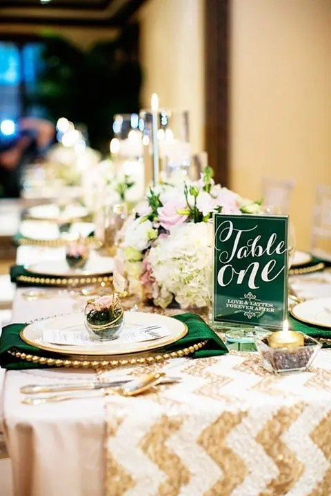 a chic table setting with a chevron gold table runner, emerald napkins and table numbes, gold cutlery and succulents