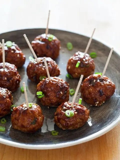 meat balls with greenery served on toothpicks is a great idea fo comfort food