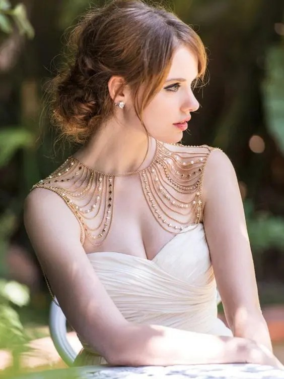 a fantastic shoulder jewelry piece with many rows of gold and pearls