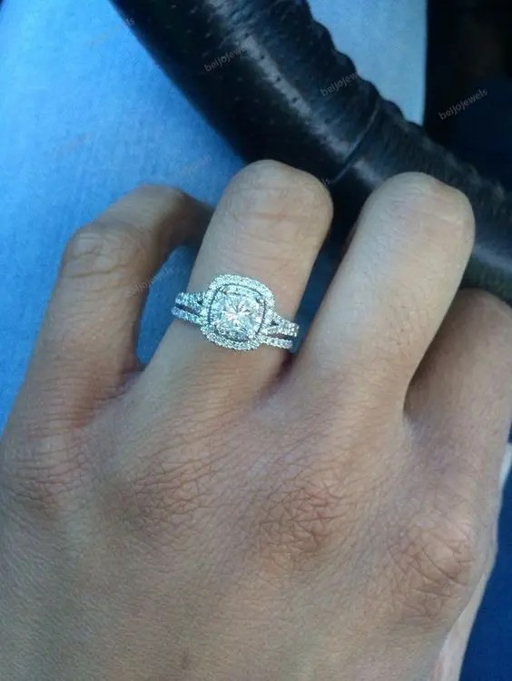 a white gold engagement ring with a cushion cut diamond and a halo
