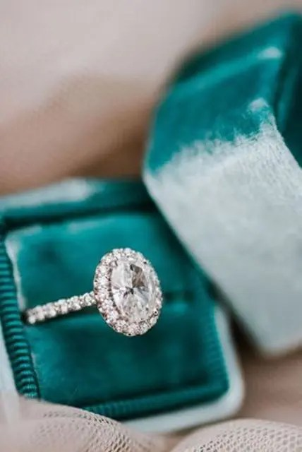 a stunning vintage-inspired oval-shaped diamond engagement ring with a halo
